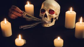 Skull with US Dollar bills in his mouth. Women`s hands pull banknotes out of the mouth of the skull. Candles are burning around the circle. Black background stock footage