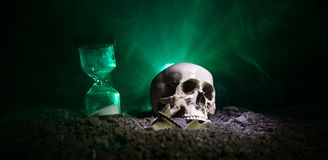 Skull and vintage hourglass on dark toned foggy background under beam of light. Horror concept. Empty space stock photo