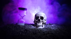 Skull and vintage hourglass on dark toned foggy background under beam of light. Horror concept. Empty space stock photography