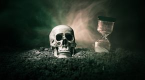 Skull and vintage hourglass on dark toned foggy background under beam of light. Horror concept. Empty space royalty free stock photography