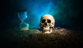 Skull and vintage hourglass on dark toned foggy background under beam of light. Horror concept. Empty space stock photos