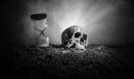 Skull and vintage hourglass on dark toned foggy background under beam of light. Horror concept. Empty space stock images