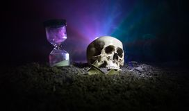 Skull and vintage hourglass on dark toned foggy background under beam of light. Horror concept. Empty space royalty free stock images