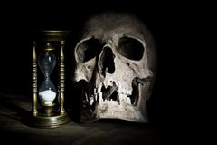 Skull and vintage hourglass on wooden background under beam of light.  royalty free stock photography
