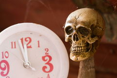 Skull waiting time on clock vintage tone Stock Photos
