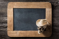 Skull wearing hat at corner of slate Royalty Free Stock Images