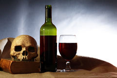 Skull And Wine. In vino veritas. Open bottle of red wine and wineglass near human skull on book stock image