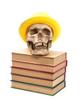 Skull in yellow hat on books Stock Photography