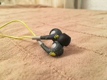 Skullcandy Earplugs. A chill photo made in bed Stock Photos