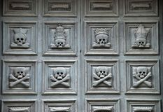 Skulls on a church door. Skulls carved on a wooden church door in Matera, Italy.  Chiesa della Purgatorio Stock Images