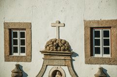 Skulls and cross carved in stone on the facade of church. Skulls and cross carved in stone between windows embellishing the facade of church in a sunny day at stock images