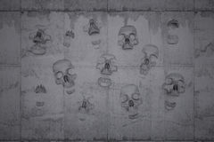 Skulls on a wall of concrete. Symbol for doom and despair Royalty Free Stock Photos