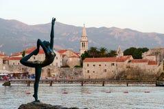Skulptera ballerina (dansare av Budva) mot bakgrunden av den gamla staden royaltyfri fotografi