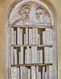 Skulptera i lättnad av en bokhylla med böcker som göras ut ur stenen eller murbruk royaltyfri foto