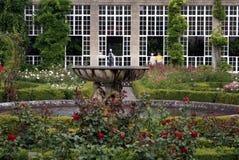 Skulpterad springbrunn i en rosträdgård Arkivbild