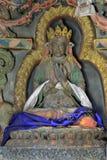Skulptur av den tibetana läraren Naropa: en grå staty i en guld- krona och med traditionella buddistiska scarves i händer och knä Royaltyfri Bild