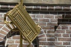Skulptur av det guld- tangentbordet med tegelstenväggen som bakgrund Royaltyfri Foto