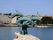 Skulptur av en delfinbanhoppning på en vagga framme av hamnen av Rhodes, Grekland Royaltyfri Bild