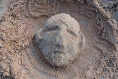 Skulptur av en mänsklig framsida vid sand Arkivfoton