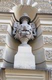 Skulptur av en vas med lejons huvud och prydnader på väggen av byggnaden royaltyfria bilder