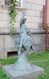 Skulptur av ett pojkesammanträde på en kagge Arkivbilder