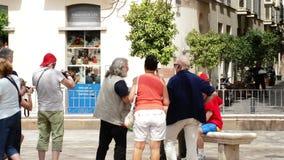 Skulptur av målaren Pablo Ruiz Picasso Malaga i en parkera i Malaga med turister fotograferade ith honom stock video
