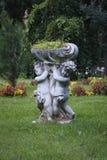 Skulptur av två barnholdinblommor fotografering för bildbyråer