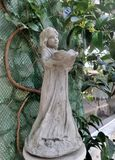 Skulptur des kleinen Mädchens und grüne Rebe im englischen Garten Lizenzfreie Stockbilder
