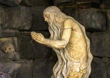 Skulptur eines betenden Schädels des alten Mannes Stockbilder