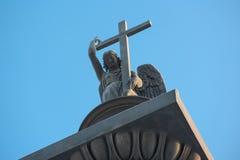 Skulptur eines Engels mit Kreuz und Schlange Stockbild