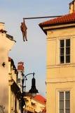 Skulptur eines hängenden Mannes in einer schmalen alten Straße in der Mitte von Prag, Tschechische Republik stockbilder