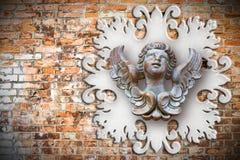 Skulptur eines hölzernen Engels gegen einen alten klassischen Gips fra Stockbild