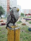 Skulptur eines Raubvogels sitzend auf einem Stumpf Stockbilder