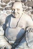 Skulptur Hotei auf Hintergrund der Steinwand Stockfotos