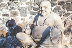 Skulptur Hotei auf Hintergrund der Steinwand Lizenzfreie Stockbilder