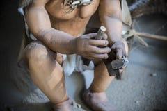 Skulptur in Lebensgröße des prähistorischen Mannes lithic Werkzeug herstellend Lizenzfreies Stockbild