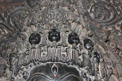 Skulptur med den sned microen välsignar skallen på den Hoysaleswara templet Royaltyfri Foto