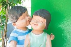 Skulpturen av att le vänder mot barnvännen arkivfoton