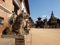Skulpturen von Löwen nahe dem Palast mit 55 Fenstern in Nepal Stockfotografie