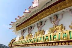 Skulpturer av buddistiska gudar och garneringar på väggarna av en buddistisk tempel royaltyfri foto