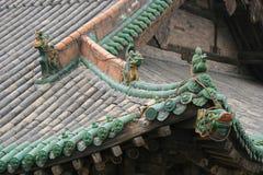 Skulpturer av fantastiska djur och glasade tegelplattor dekorerar taket av en tempel (Kina) Arkivfoto