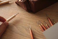 Skulpturwerkzeugc$t-ball und brauner Lehm auf dem Tisch Lizenzfreie Stockbilder