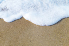 Skumhav på sandbakgrunden Arkivfoto