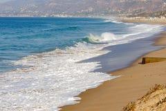 Skumma blekna vågen på sandig shoreline, våg som krönar och att skumma svallvåg som krönar vågor ner shoreline, arkivfoton
