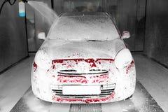 Skumma den röda automatiskn på biltvätt fotografering för bildbyråer