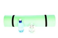 Skumma matt rulle för yoga med flaskan av vatten på vit Fotografering för Bildbyråer