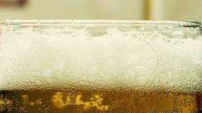 Skumma upp öl i ett exponeringsglasbägareslut lager videofilmer