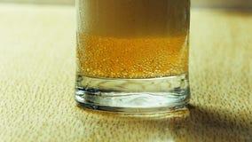 Skumma upp öl i ett exponeringsglasbägareslut arkivfilmer