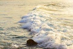 Skumma vågen som bryter på soluppgång med färgreflexion arkivfoto