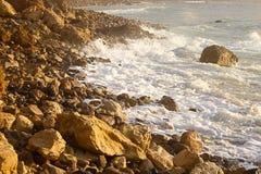 Skumma v?gen som bryter p? soluppg?ng med stenig shoreline arkivbild